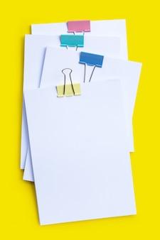 Apilamiento de documentos comerciales con coloridos clips de encuadernación en superficie verde