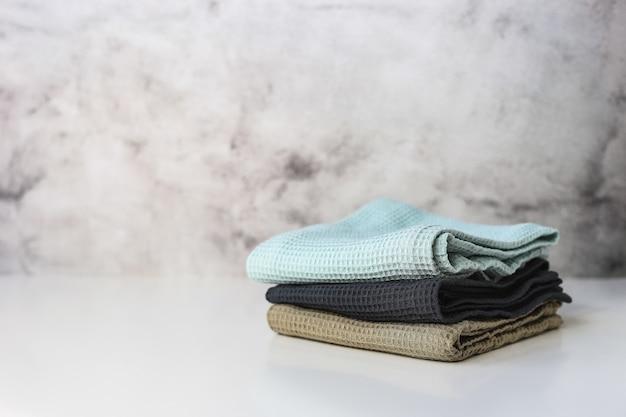 Apilar toallas de cocina de algodón sobre fondo gris.