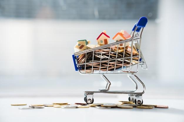 Apile las monedas y la mini casa en el carrito de la compra utilizando como propiedad inmobiliaria y el concepto de marketing empresarial