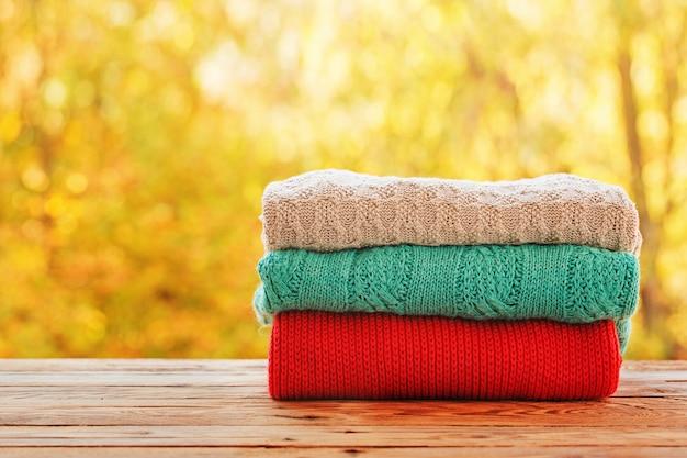 Apile la pila de ropa hecha punto del otoño en la naturaleza al aire libre.