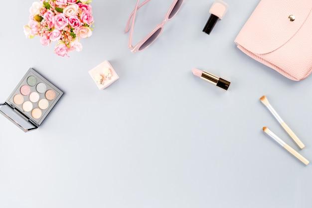 Aplanada con cosméticos, cartera, libro de planificador y flores.