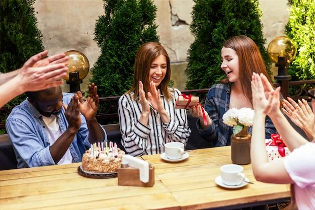 Aplausos y regalos de cumpleaños de los mejores amigos en la fiesta de celebración en la terraza del café