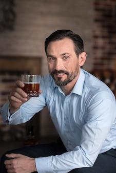 Aplausos para usted. apuesto hombre alegre encantado sosteniendo un vaso lleno de whisky y sonriendo mientras te mira