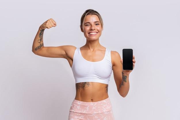 Aplicación de entrenamiento. ajuste a una mujer bonita que muestra un teléfono inteligente con una aplicación de fitness moderna para realizar un seguimiento de la actividad deportiva. posando sobre la pared amarilla del estudio.