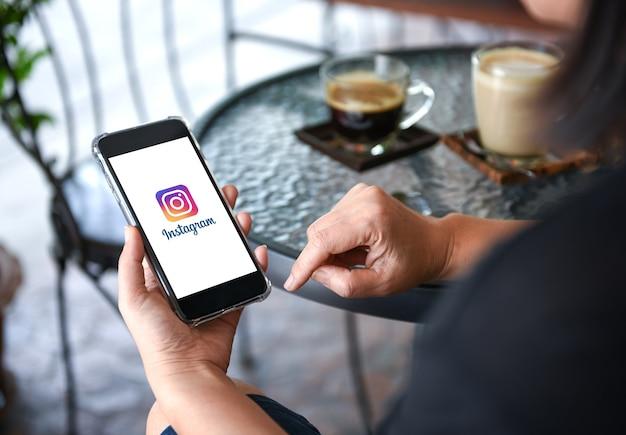 Aplicación de instagram en pantalla de teléfono inteligente en la mano con café en el fondo de la mesa
