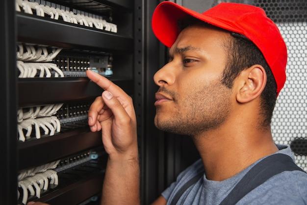 Aplicación interior. ingeniero de ti concentrado levantando la mano mientras mira el armario del servidor