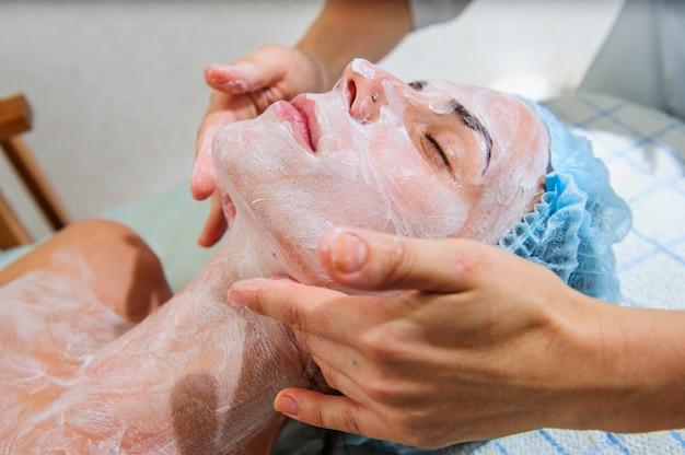 Aplicación de máscaras doradas en la cara del modelo. procedimientos cosméticos.