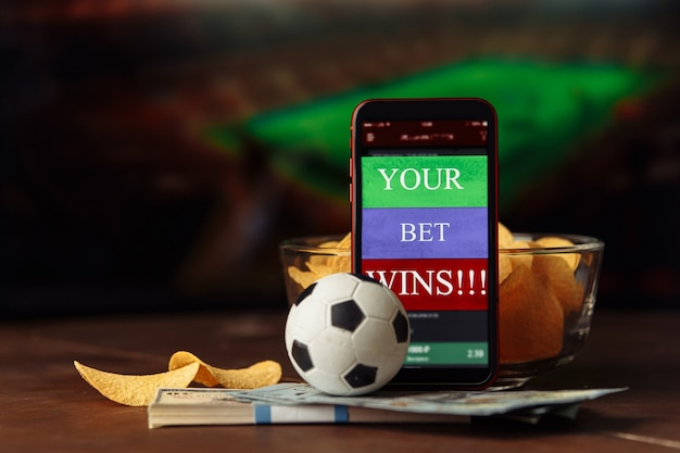 Aplicación móvil para apuestas online y balón de fútbol con snacks.
