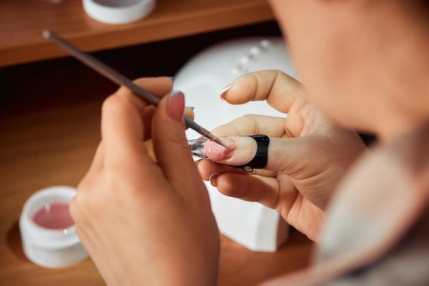 Aplicando el esmalte de uñas en gel, la mujer haciendo la manicura.