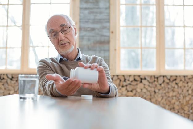 Apoya tu salud. tranquilo hombre mayor seguro con gafas mientras coloca pastillas en la mano y mira hacia abajo