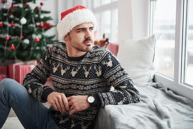 Apoyado en el alféizar de la ventana. la foto del hombre en el sombrero de santa y la ropa de vacaciones mira por la ventana. árbol de navidad en el fondo