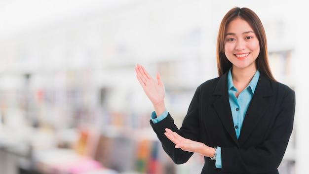 Apoyo al cliente sonriente hermoso asiático de la empresaria en alameda de compras de la falta de definición.