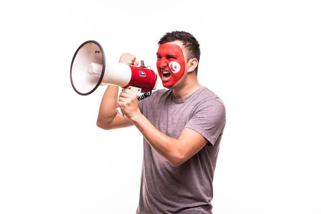 Apoyo del ventilador del equipo nacional de túnez con la cara pintada gritar y gritar en megáfono aislado sobre fondo blanco.
