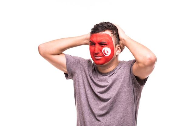 El apoyo del ventilador perdedor molesto del equipo nacional de túnez con la cara pintada aislado sobre fondo blanco.