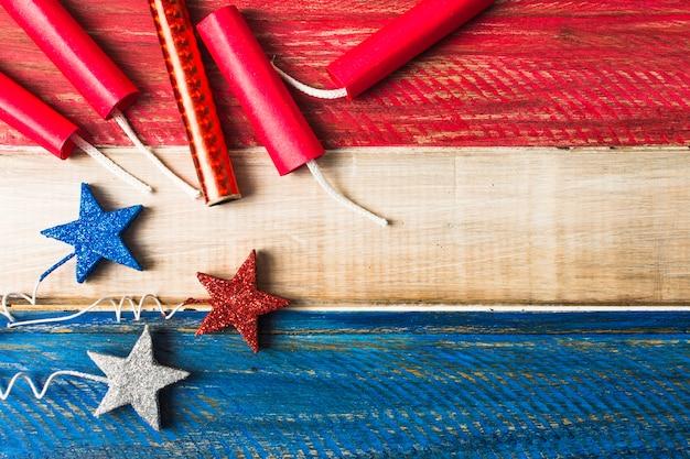 Apoyos de estrellas y petardos de dinamita sobre fondo de madera pintado de rojo y azul