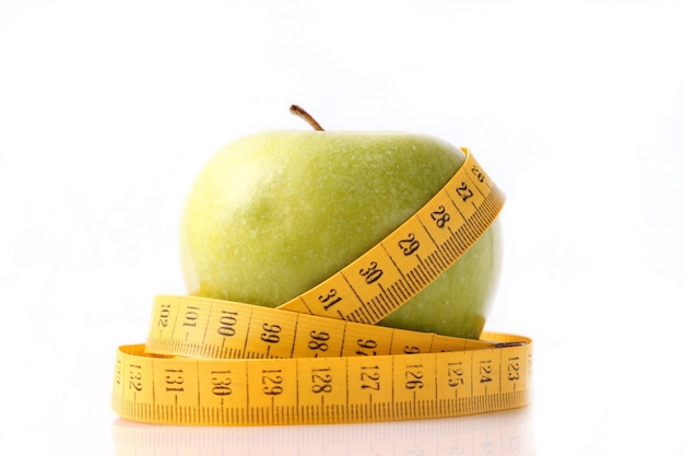Apple y primer plano de cinta métrica sobre un fondo claro