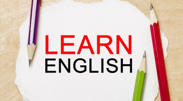 Aprende inglés en un bloc de notas blanco con lápices sobre un fondo de madera. concepto de negocio