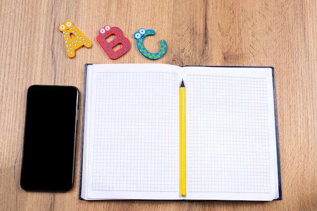 Aprender el estilo de vida de una lengua extranjera en el concepto de escuela en línea en la mesa de madera y la pantalla vacía en negro