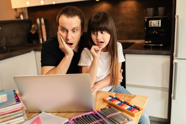 Aprender en línea. la colegiala y su padre miran una lección de video en la computadora portátil en casa. educación a distancia. convivencia familiar
