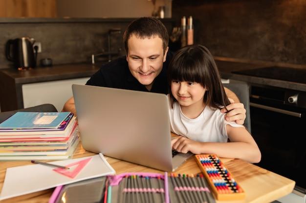 Aprender en línea. unión familiar al hacer la tarea. padre ayuda a su hija a hacer una lección en línea en casa