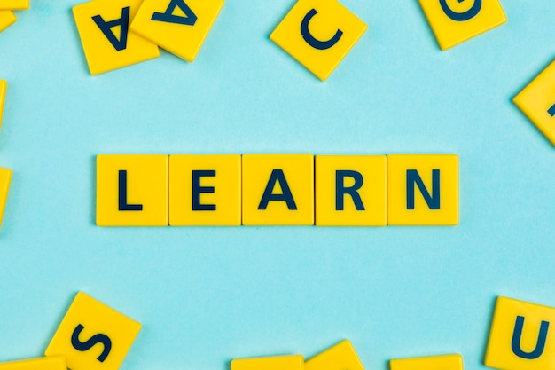 Aprender la palabra en las baldosas de scrabble