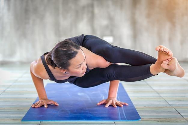 Aprendiz asiática mujer fuerte practicando yoga difícil plantean en un fondo concreto