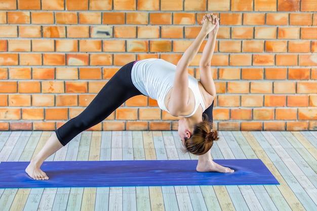 Aprendiz asiática mujer fuerte practicando yoga difícil plantear