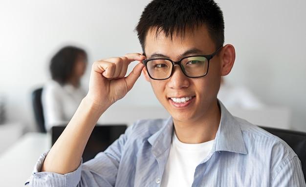Aprendiz masculino étnico en ropa casual sonriendo y ajustando gafas mientras trabaja en la oficina de la empresa de ti