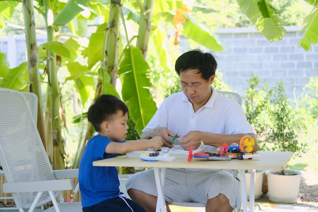 Aprendizaje basado en el hogar (hbl), padres sentados, educación en el hogar con un niño pequeño, padre e hijo asiáticos que se divierten haciendo fáciles botes de juguete stem para estudiantes en casa, juguetes educativos para niños pequeños