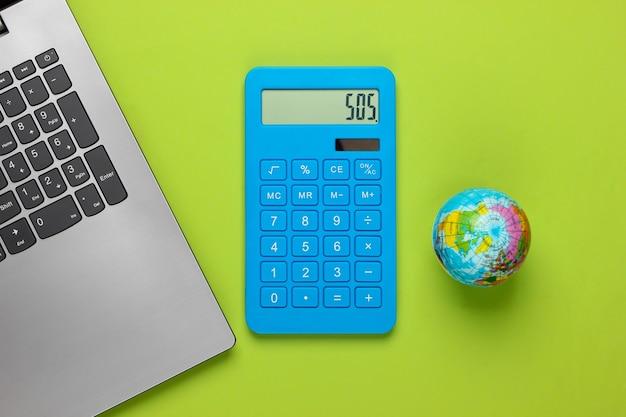 Aprendizaje, concepto ecológico. computadora portátil, calculadora con un globo en un verde