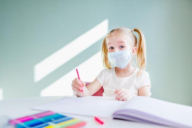 Aprendizaje escolar en casa durante la pandemia de virus. niña dibujando en casa, usando mascarillas quirúrgicas para protegerse del virus. copyspace