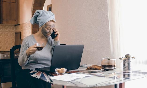 Aprendizaje independiente femenino europeo a distancia durante el distanciamiento social del virus corona y hablar por teléfono móvil. trabajar desde casa durante la cuarentena covid-19