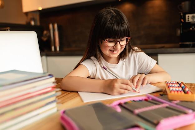 Aprendizaje en línea en casa. colegiala con gafas hace la tarea. educación a distancia durante la cuarentena