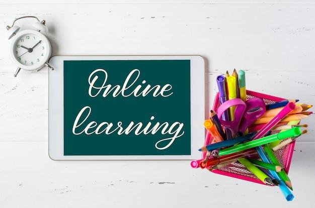 Aprendizaje en línea: inscripción manuscrita en una tableta. el concepto de formación a distancia para niños. suministros de oficina y tableta sobre un fondo de madera blanca.