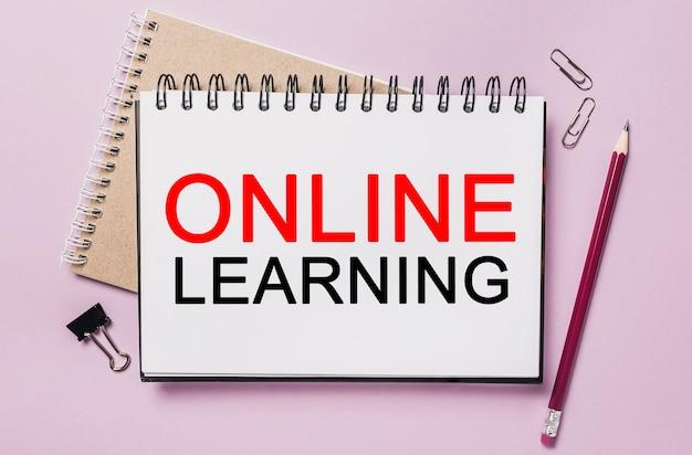 Aprendizaje en línea de texto en una pegatina blanca con fondo de papelería de oficina. lay flat en concepto de negocios, finanzas y desarrollo