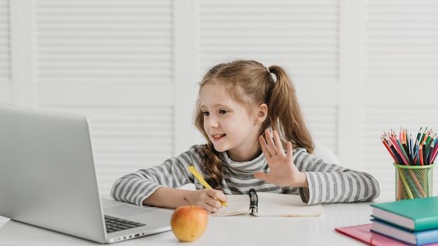 Aprendizaje de niña de vista frontal y ondas de clases en línea