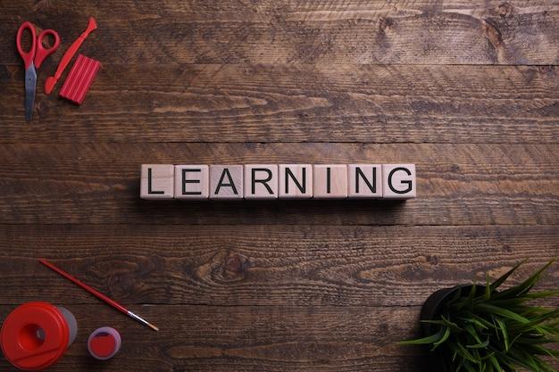 Aprendizaje de palabras en cubos de madera, bloques sobre el tema de la educación, el desarrollo y la formación en una mesa de madera. vista superior.