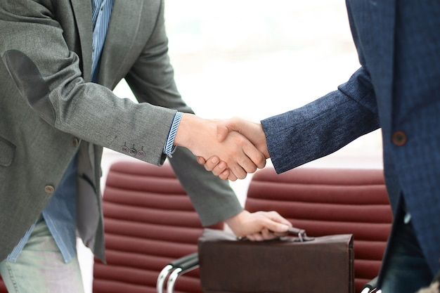 Apretón de manos del abogado con el cliente antes de la reunión.