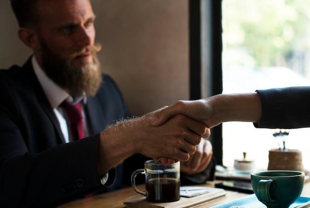Apretón de manos de acuerdo comercial en la cafetería