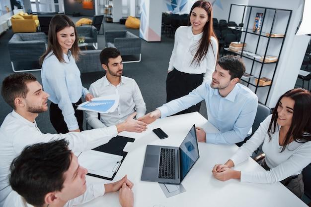 Apretón de manos para el acuerdo de éxito. vista superior de los trabajadores de oficina en ropa clásica sentados cerca de la mesa usando una computadora portátil y documentos