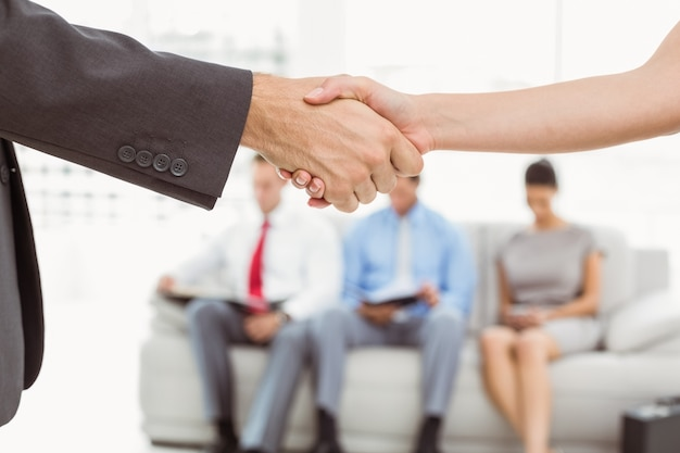 Apretón de manos además de personas esperando la entrevista