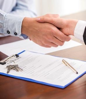 Apretón de manos de un agente inmobiliario y un cliente.