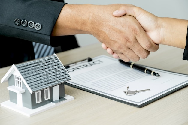 Apretón de manos el agente inmobiliario explica el contrato comercial a la mujer compradora.