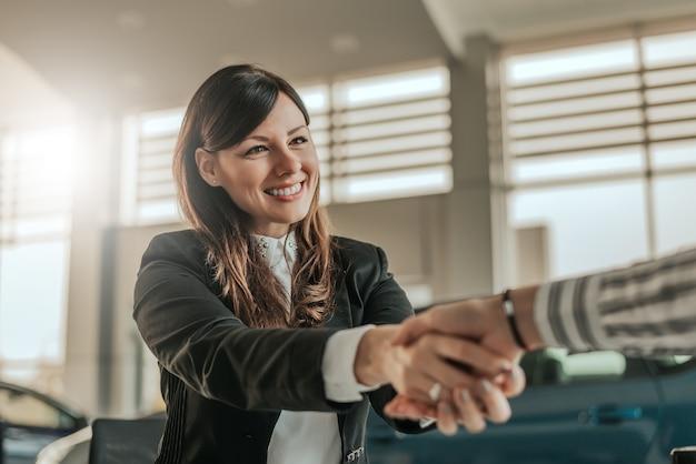 Apretón de manos alegre del concesionario de automóviles con el cliente en la sala de exposición.