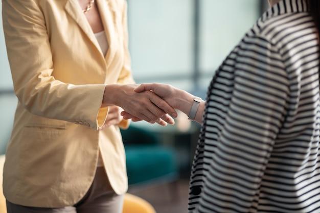 Apretón de manos amistoso. toma recortada de dos mujeres empresarias caucásicas en la oficina usan un apretón de manos mientras están de pie en la oficina