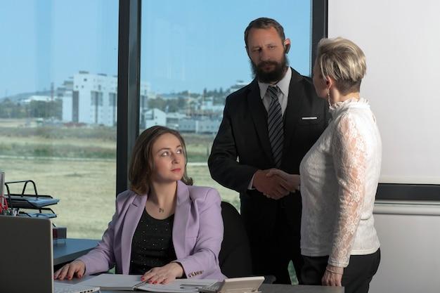 Apretón de manos: el asesor saluda a su clienta. hombre y mujer dándose la mano para saludar en la oficina. los negociadores. equipo de joven diseñador discutiendo sobre un nuevo proyecto en la oficina moderna