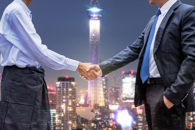 Apretón de manos de asociación de empresario de la comunidad económica de la asean en el fondo de la ciudad