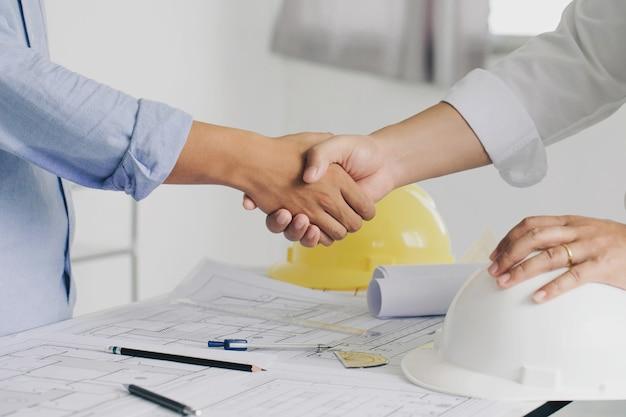 Un apretón de manos de la colaboración de ingeniería de construcción o arquitecto discutir un plano