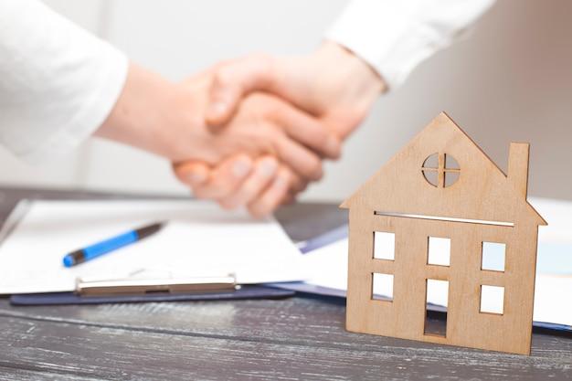 Apretón de manos bajo un contrato de bienes raíces entre un agente de bienes raíces y un cliente.