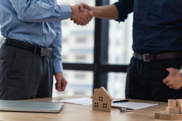 Apretón de manos después de la compra de la casa de contacto firmada o alquiler en la oficina del agente inmobiliario